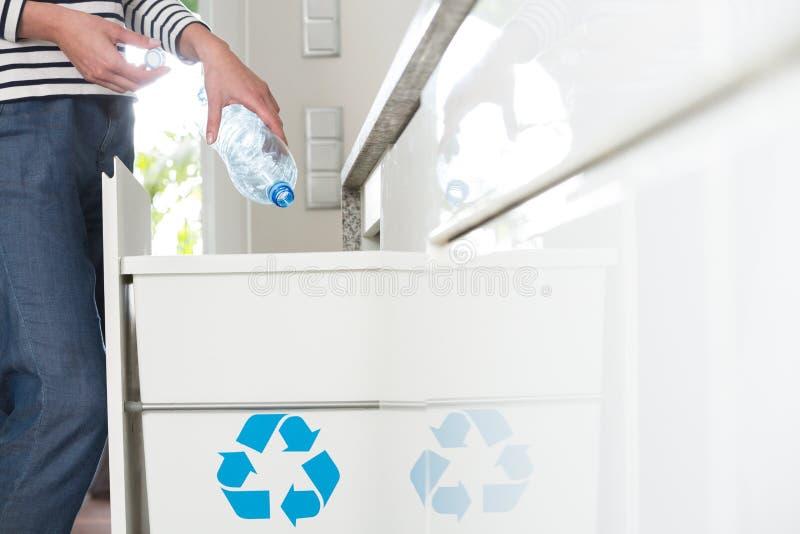 Casalinga informata che segrega le bottiglie di plastica fotografia stock libera da diritti