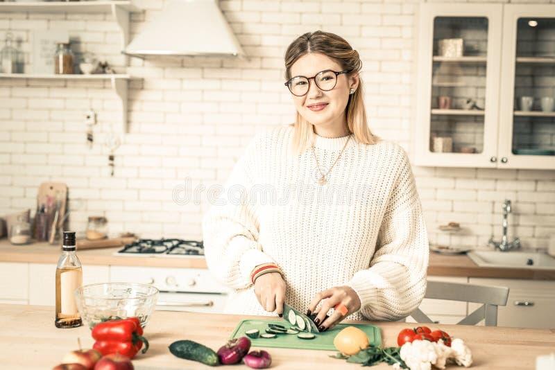 Casalinga positiva sorridente che tratta con le verdure mentre cucinando fotografie stock