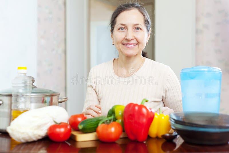 Casalinga sorridente che cucina il pranzo della verdura fotografia stock libera da diritti