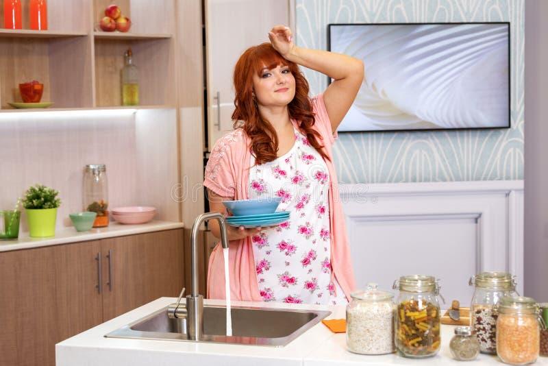 Casalinga stanca dei piatti di lavaggio in cucina fotografie stock libere da diritti