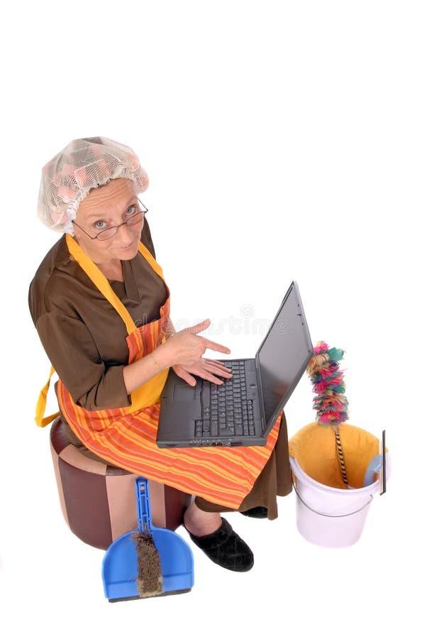 Casalinga sul computer portatile immagini stock