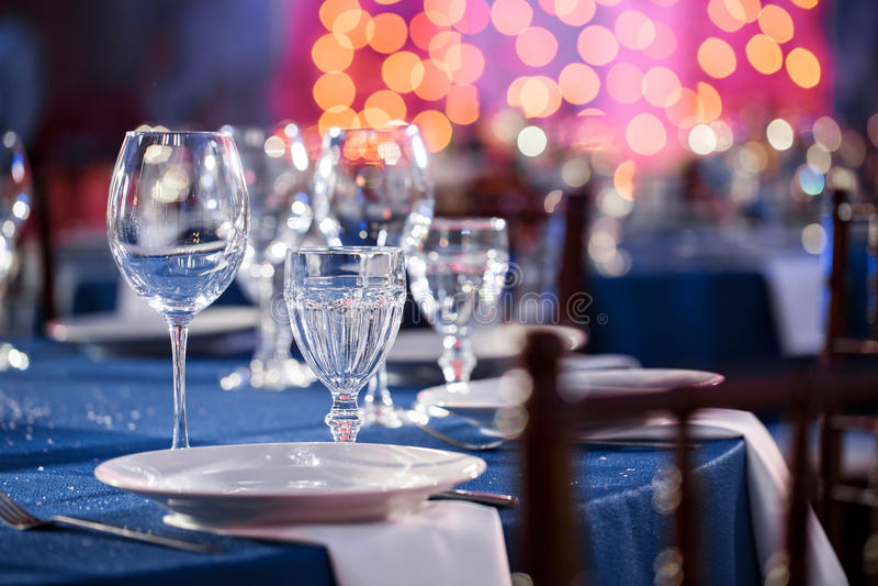 casamento banquet As cadeiras e a mesa redonda para convidados, servidas com cutelaria e louça e cobertas com um azul foto de stock royalty free