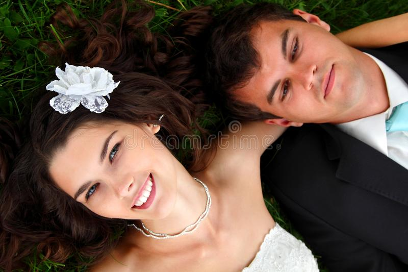 Casamento, noivos novos no amor que encontra-se na grama verde imagem de stock