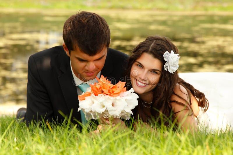 Casamento, noivos novos no amor que encontra-se na grama verde imagem de stock royalty free