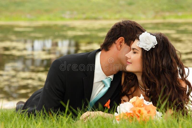 Casamento, noivos novos no amor que encontra-se na grama verde, foto de stock royalty free