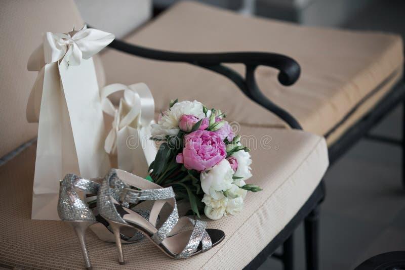 casamento O ramalhete de flores cor-de-rosa, brancas e de hortaliças está em uma cadeira contra ao lado das sapatas do ` s da noi foto de stock royalty free