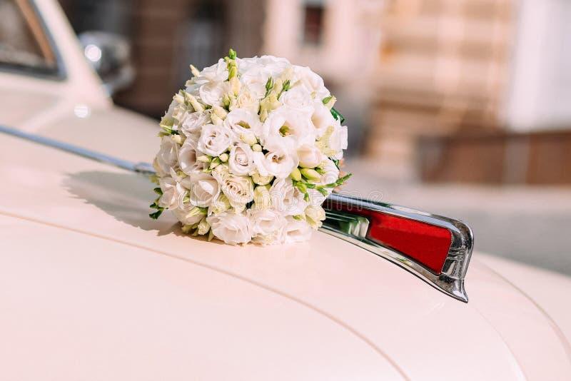 casandose el coche retro blanco de la capilla del ramo afuera imagenes de archivo