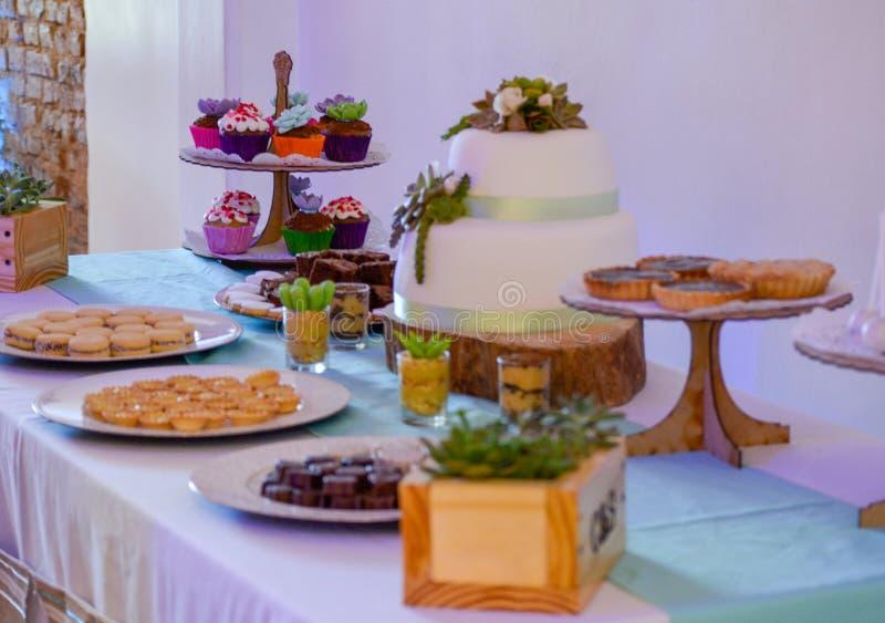 Casandose el postre dulce de la tabla del azúcar de la comida del chocolate las magdalenas sabrosas y deliciosas apelmazan el par fotografía de archivo libre de regalías