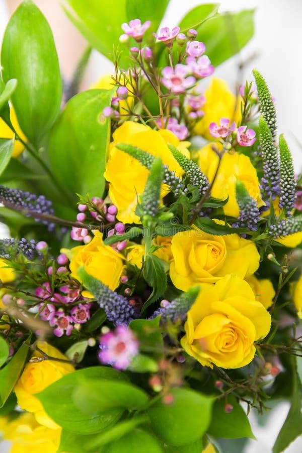 Casandose el ramo amarillo en el ` s de la novia da el fondo blanco foto de archivo libre de regalías