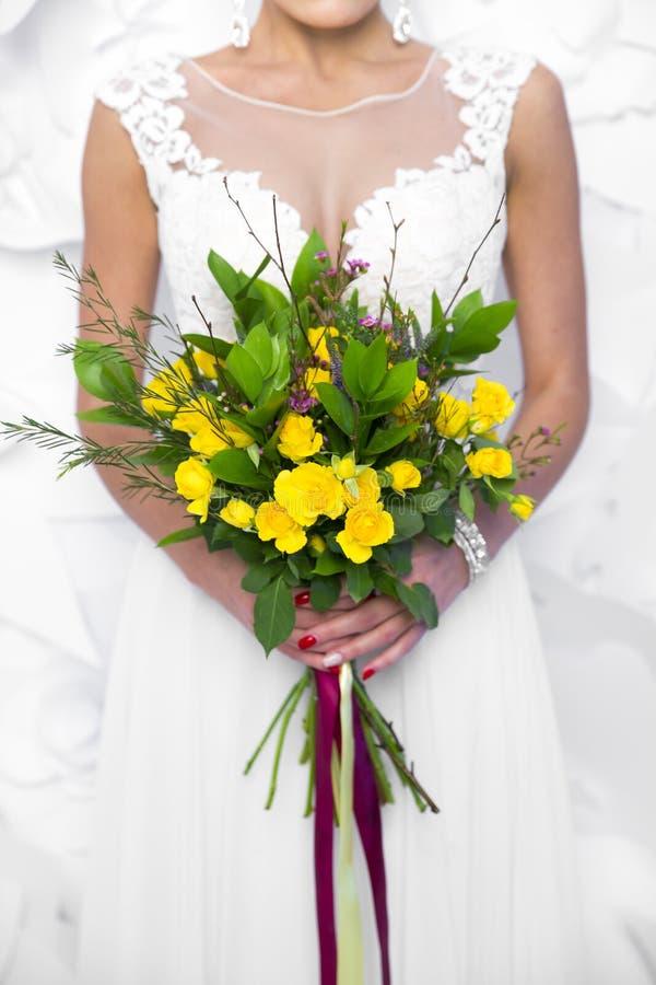 Casandose el ramo amarillo en el ` s de la novia da el fondo blanco imagen de archivo
