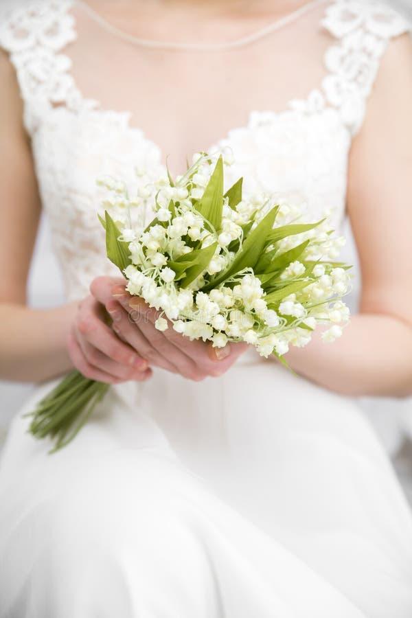 Casandose el ramo blanco en el ` s de la novia da el fondo blanco imagen de archivo
