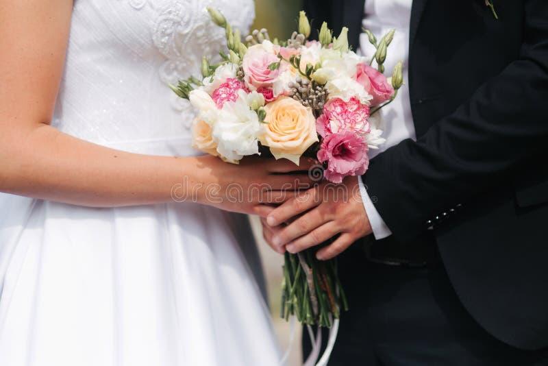 Casandose el ramo en manos de los pares afuera Flores fotografía de archivo libre de regalías