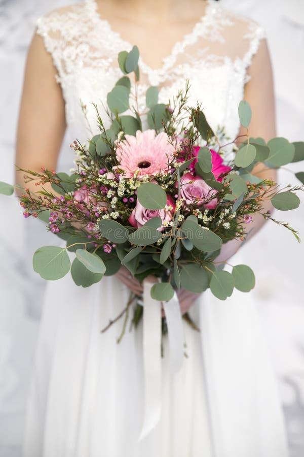Casandose el ramo rosado en el ` s de la novia da el fondo blanco fotos de archivo libres de regalías