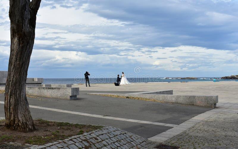 Casarse al fotógrafo que trabaja en una 'promenade' de la playa Puesta del sol, cielo gris nublado La Coruna, España fotos de archivo