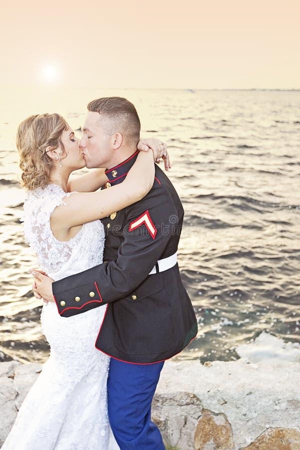 Casarse beso en la puesta del sol foto de archivo