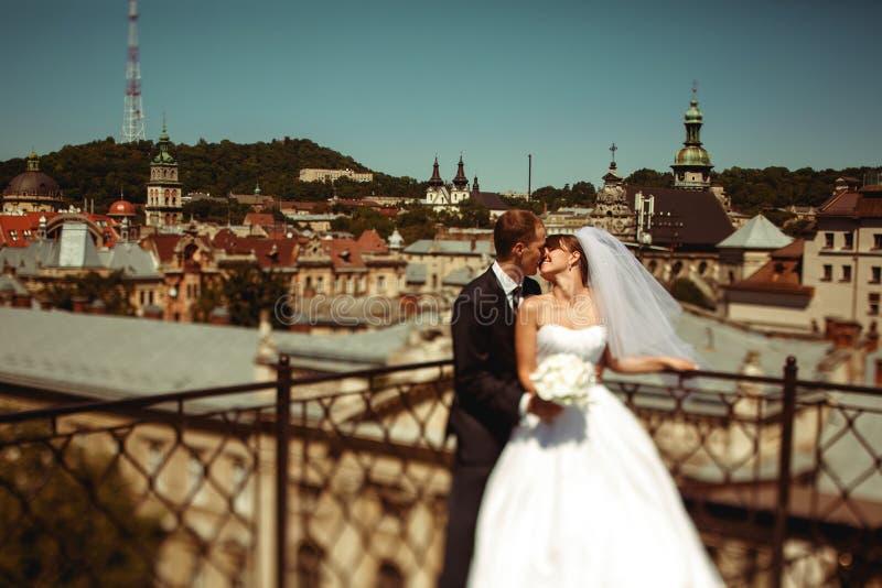Casarse besos de los pares en el frente de un gran paisaje urbano en Lviv imagen de archivo