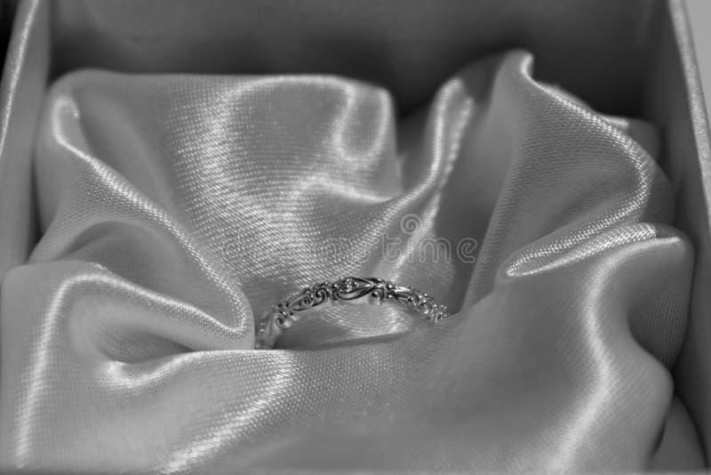 Casarse el oro brillante o el anillo de plata en una caja de regalo con el fondo de la seda del satén fotos de archivo