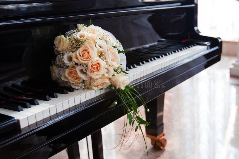 Casarse el ramo de rosas miente en las llaves del piano de cola imagenes de archivo