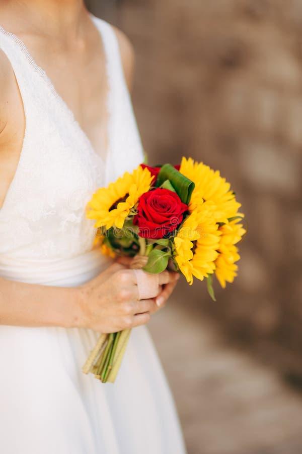 Casarse el ramo nupcial de girasoles en las manos de la novia fotos de archivo