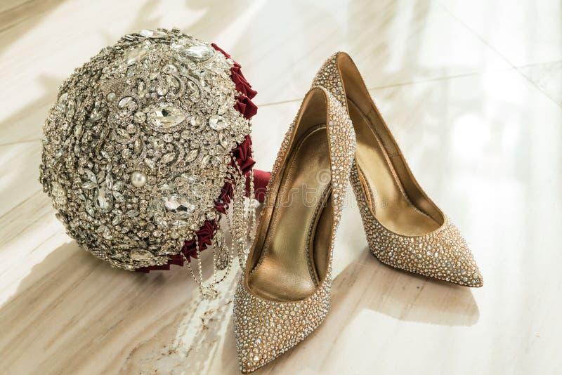 Casarse el ramo y los zapatos de oro de la novia con las piedras en el piso de las tejas de mármol fotografía de archivo