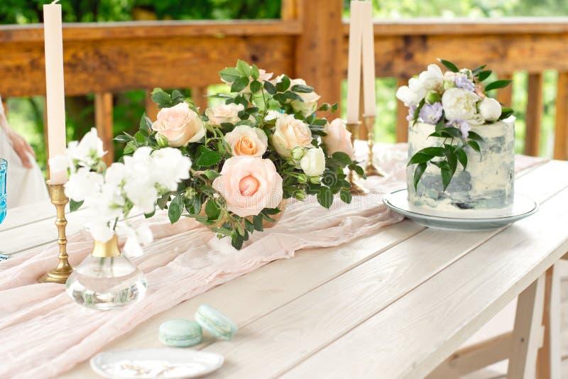 Casarse la tabla de la decoración en el jardín, arreglo floral, velas en el vintage del estilo en al aire libre Torta de boda con imágenes de archivo libres de regalías