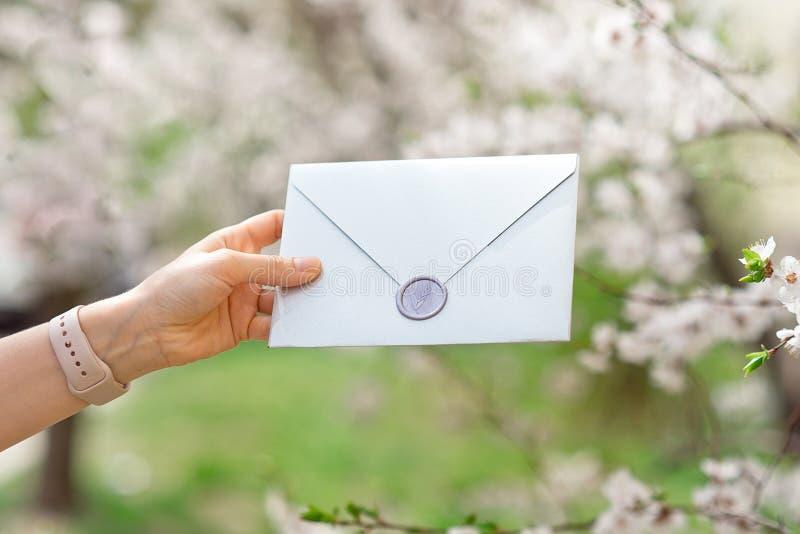 Casarse las hojas de las tarjetas de la invitación, de los sobres del arte, del rosa y blancas del flor y verdes en el fondo bla imagen de archivo