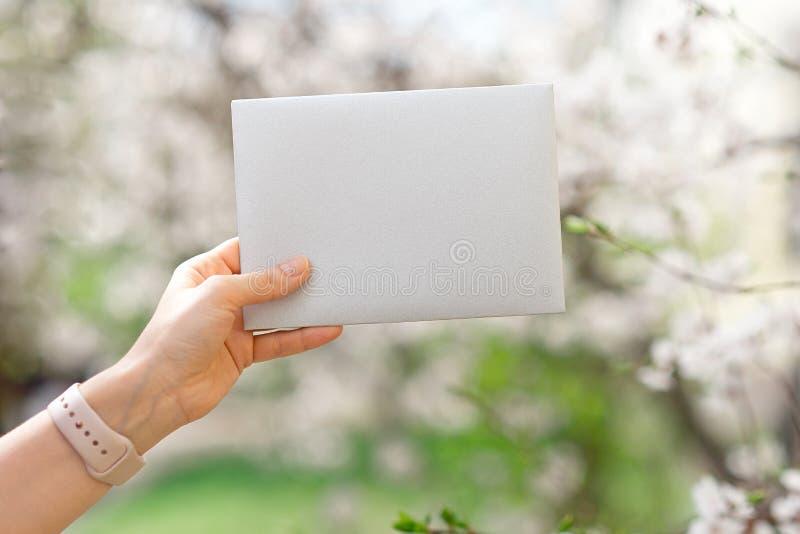 Casarse las hojas de las tarjetas de la invitación, de los sobres del arte, del rosa y blancas del flor y verdes en el fondo bla fotos de archivo
