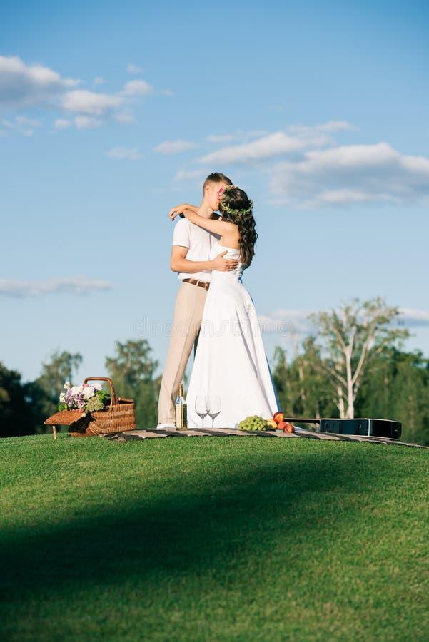 casarse los pares que abrazan y que se besan en césped verde imagenes de archivo