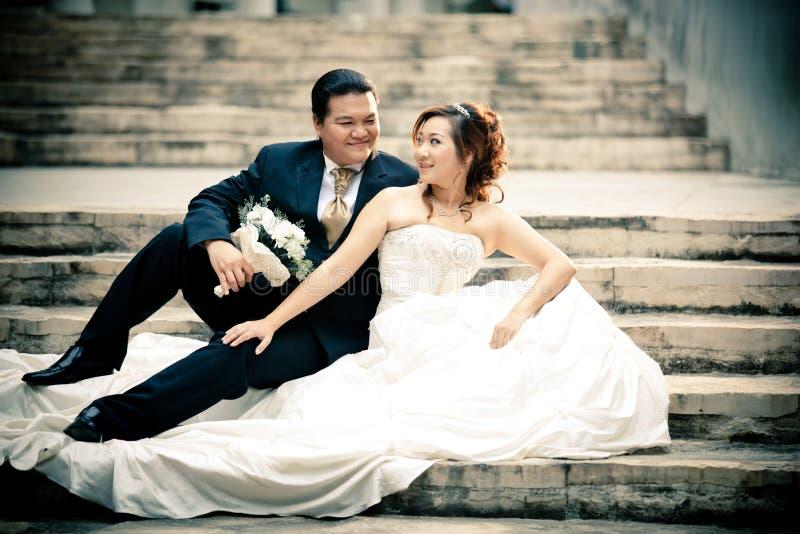 Casarse los pares que disfrutan de exteriores rom?nticos de los momentos en un verano Novia y novio felices en su boda fotos de archivo