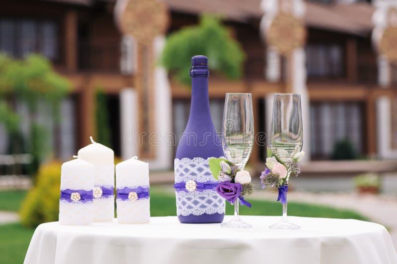 Casarse los vidrios y las botellas adornados del champán en la tabla fotografía de archivo