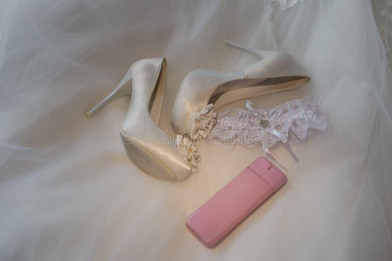 Casarse los zapatos y los perfumes de las mujeres en el vestido imagen de archivo libre de regalías