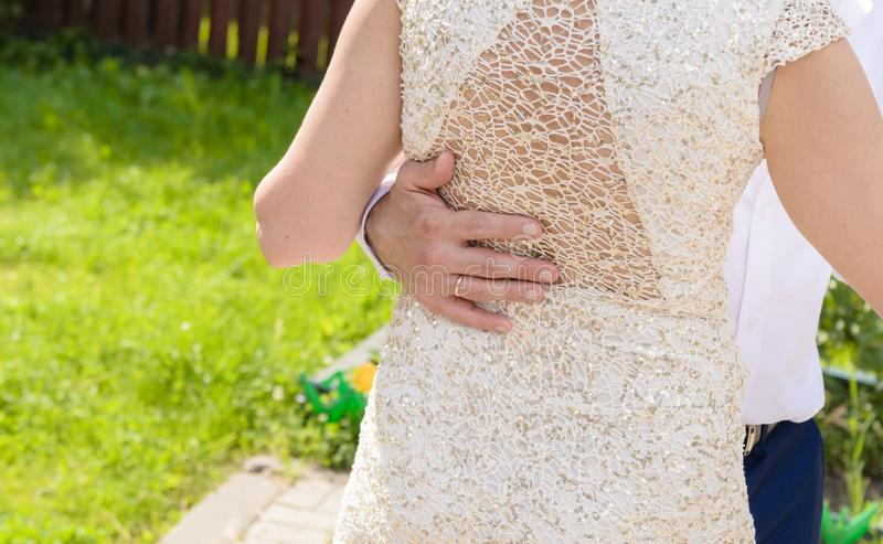 Casarse pares celebra las manos mientras que baila La mano del novio en la parte posterior de la novia fotografía de archivo