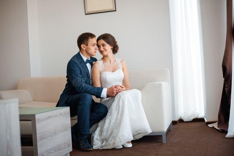 Casarse pares dentro se está abrazando fotos de archivo