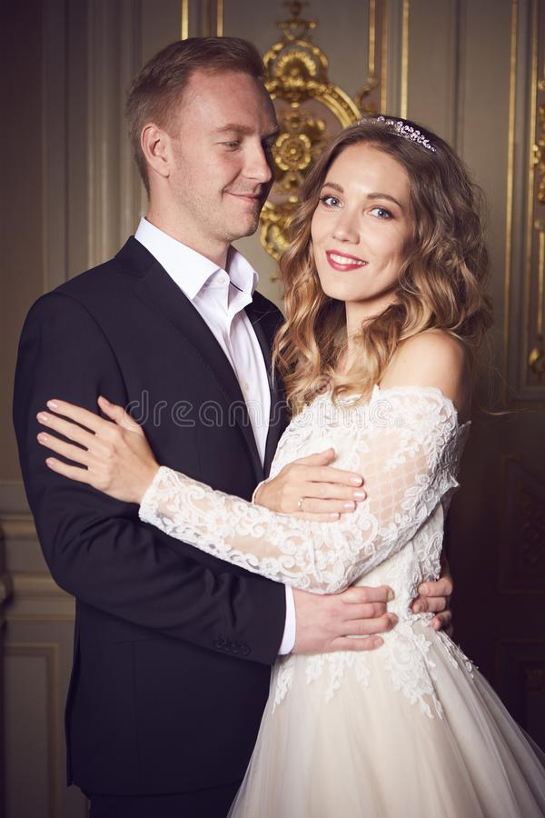 Casarse pares dentro se está abrazando Muchacha modelo hermosa en el vestido blanco Hombre en traje Novia de la belleza con el no fotos de archivo libres de regalías