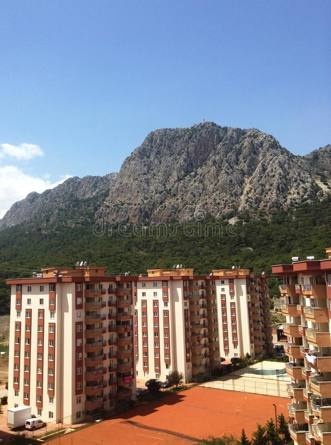 Casas altas da cidade no fundo de montanhas verdes em Antalya fotografia de stock