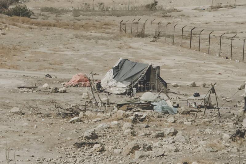 Casas beduinas en el desierto cerca del mar muerto Regiones pobres del mundo Un beduino indigente que se sienta en la tienda Pobr fotografía de archivo