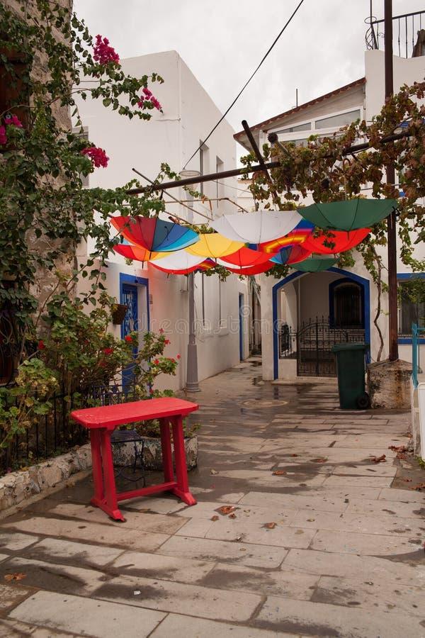 Casas blancas en el estilo griego Las calles estrechas de Bodrum Se dirige a residentes Colgante colorido de los paraguas al revé imagen de archivo