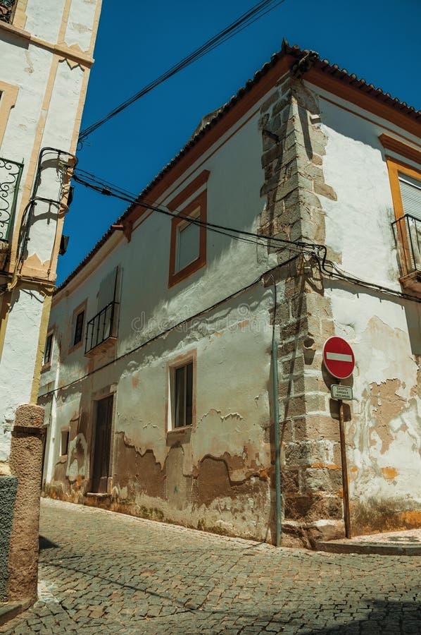 Casas brancas com descascamento do emplastro e do NENHUM sinal de estrada da ENTRADA fotografia de stock