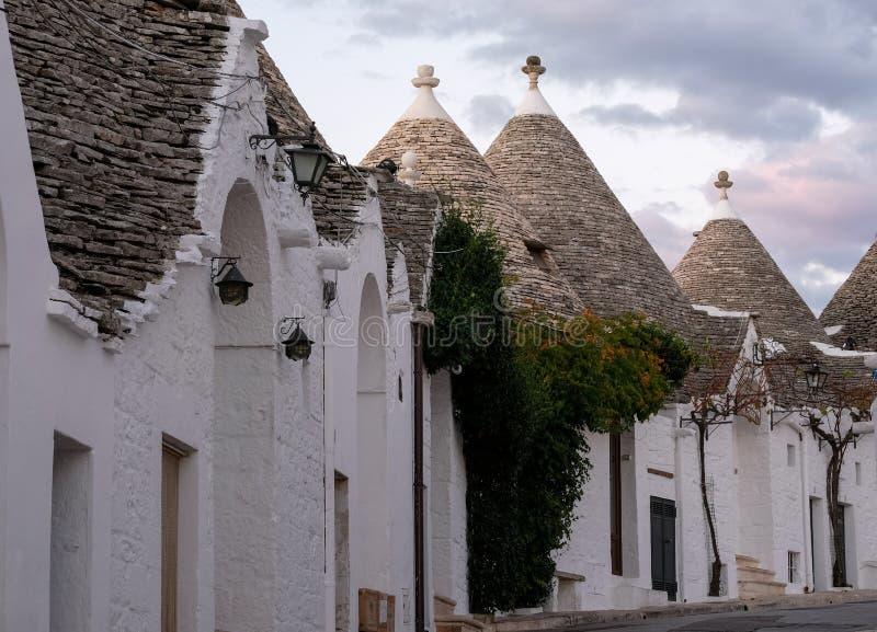 Casas cônico-telhadas branco-lavadas tradicionais na área de Rione Monti da cidade de Alberobello em Puglia, Itália sul imagens de stock