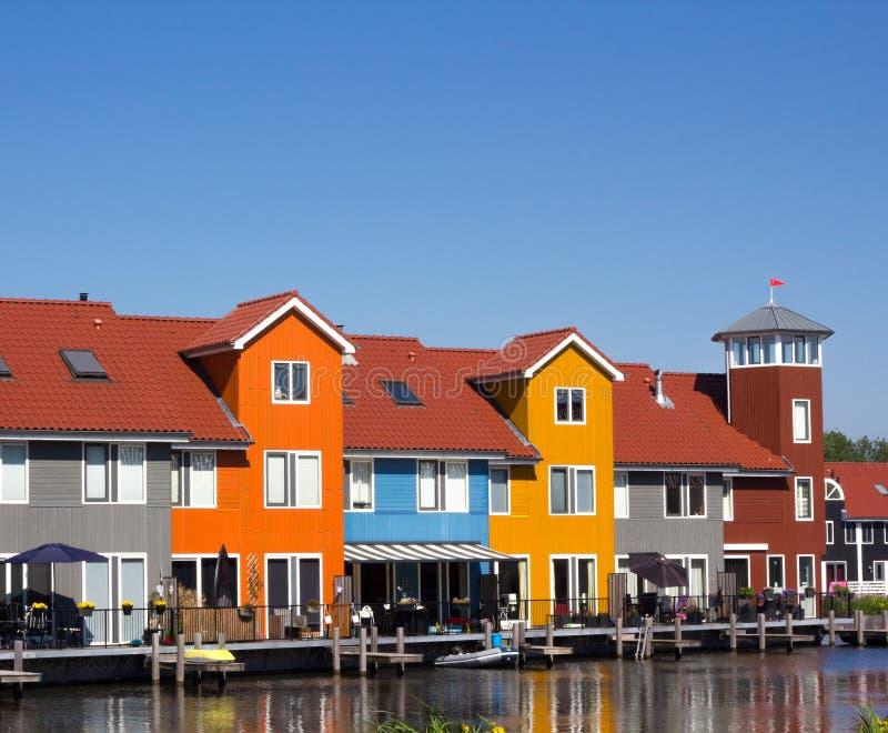 Casas coloreadas con el embarcadero cerca del agua fotografía de archivo