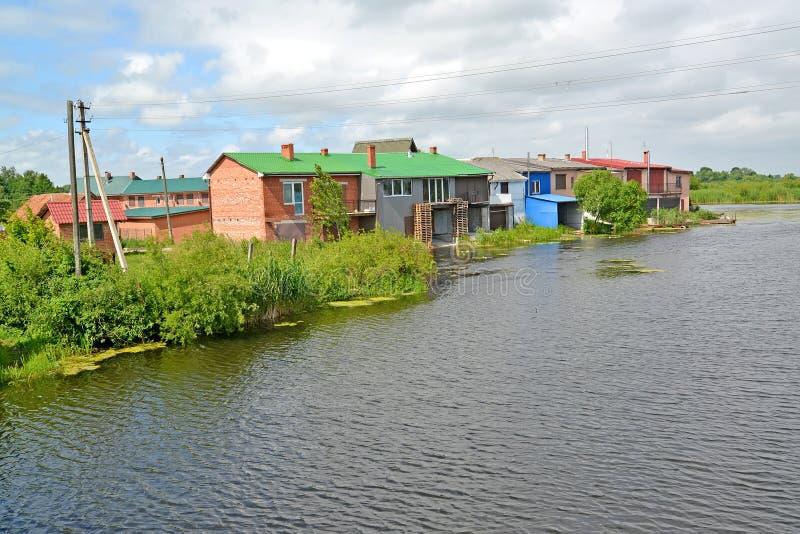 Casas com as vertentes no banco de rio de Deyma Polessk, região de Kaliningrad fotografia de stock