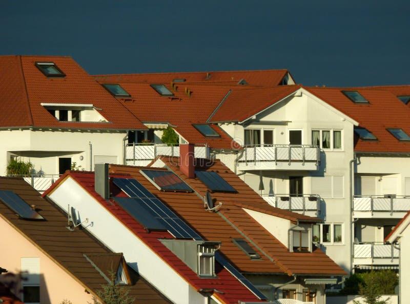 Casas com os telhados fachada-vermelhos brancos e escuro modernos - céu azul imagem de stock royalty free