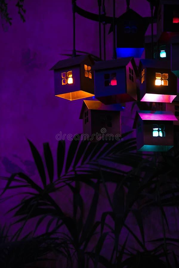 Casas con las luces dentro en un fondo púrpura foto de archivo libre de regalías