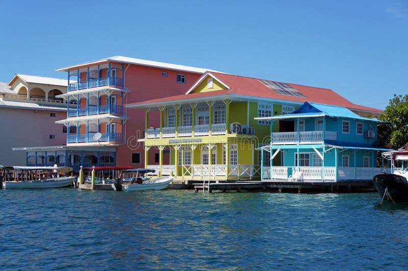 Casas das caraíbas coloridas sobre a água com barcos fotografia de stock