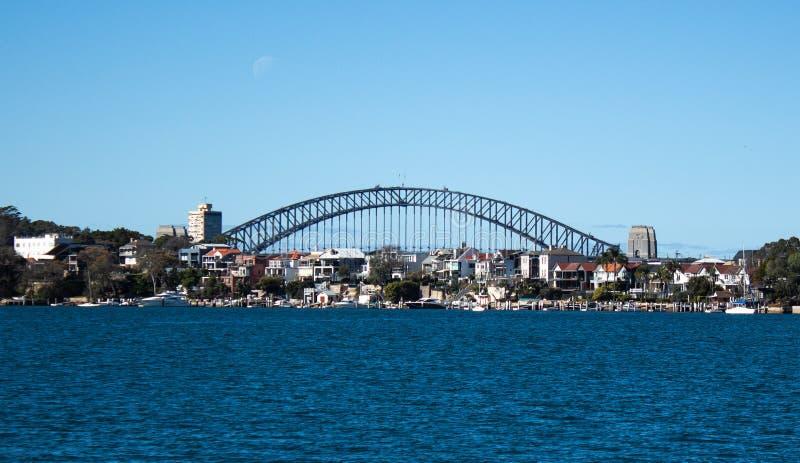 Casas de Harbourside de la ciudad en el punto Birchgrove Sydney Australia de Robinsons con el puente del puerto en fondo contra e fotografía de archivo libre de regalías