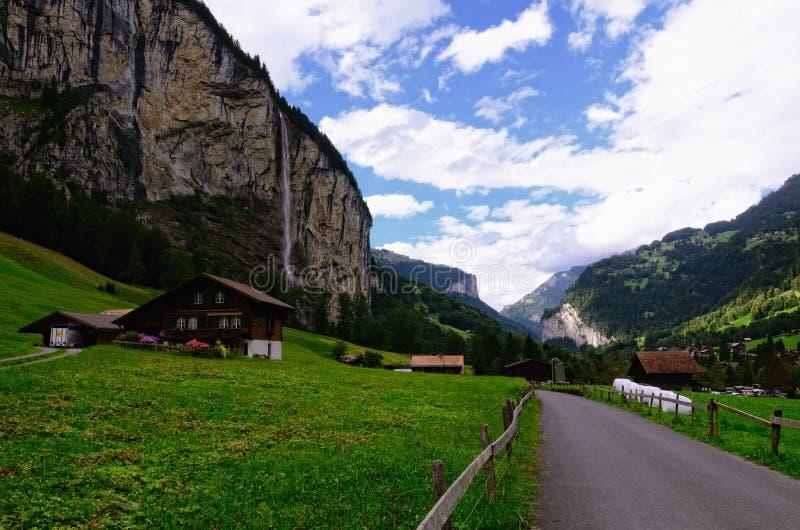 Casas de la carretera nacional y de la granja en el valle de Lauterbrunnen y x28; Región de Jungfrau, suizo Alps& x29; foto de archivo