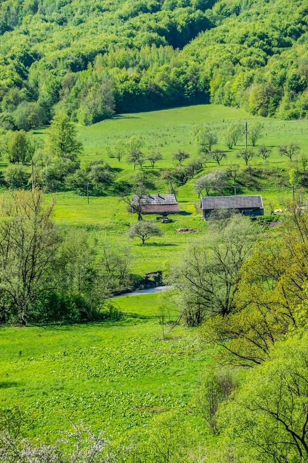 Casas de la granja en un valle verde fotos de archivo