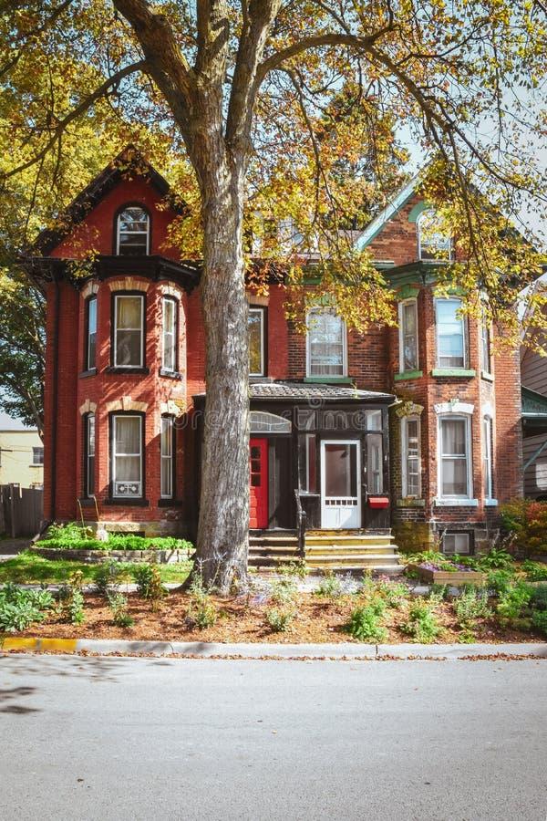 Casas de ladrillo rojo y techos de mansard con jardín y árbol en otoño Gananoque (Canadá) foto de archivo