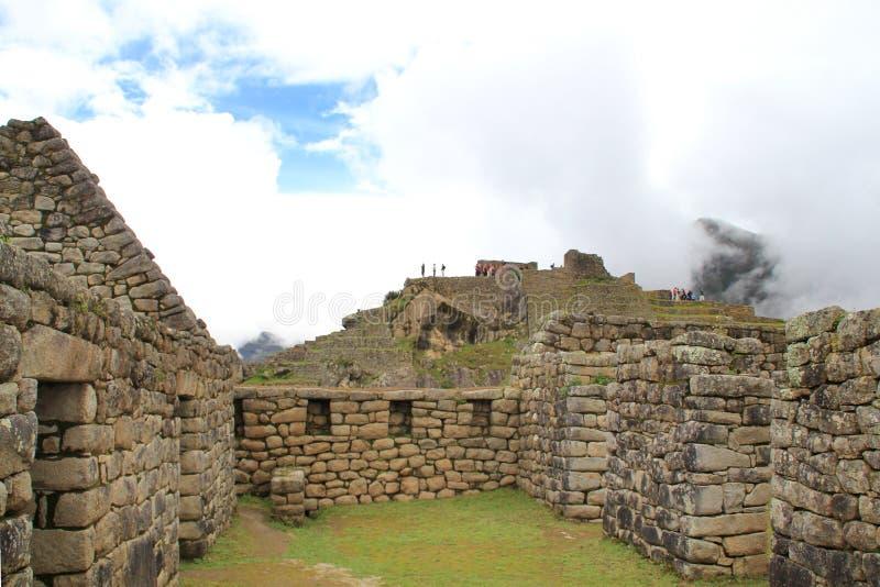 Casas de Machu Picchu sob o céu azul nebuloso foto de stock royalty free
