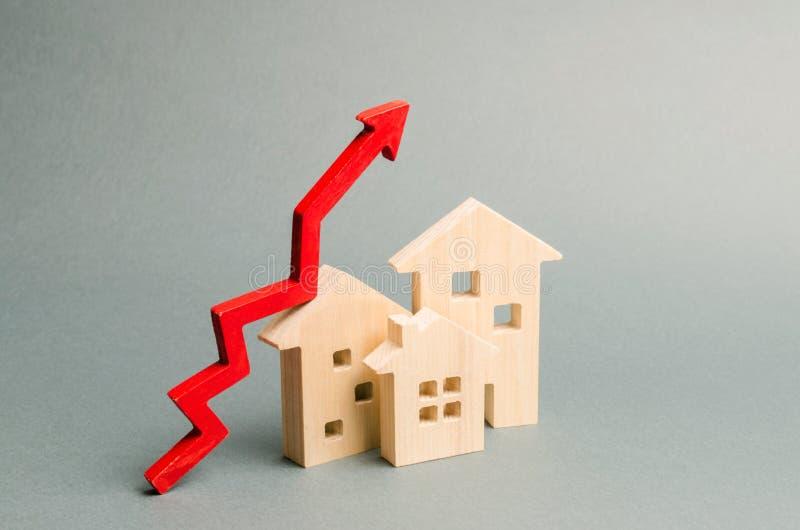 Casas de madeira diminutas e seta vermelha acima O conceito de aumentar o custo do alojamento Alta demanda para bens imobili?rios imagens de stock royalty free